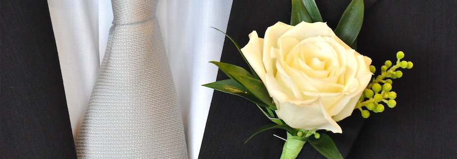 Perfect White Rose Bou­ton­nière on Tux by Flower Duet