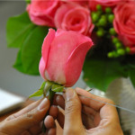 Flower Duet flower arranging student placing a wire through a hot pink rose stem to make a boutonniere.