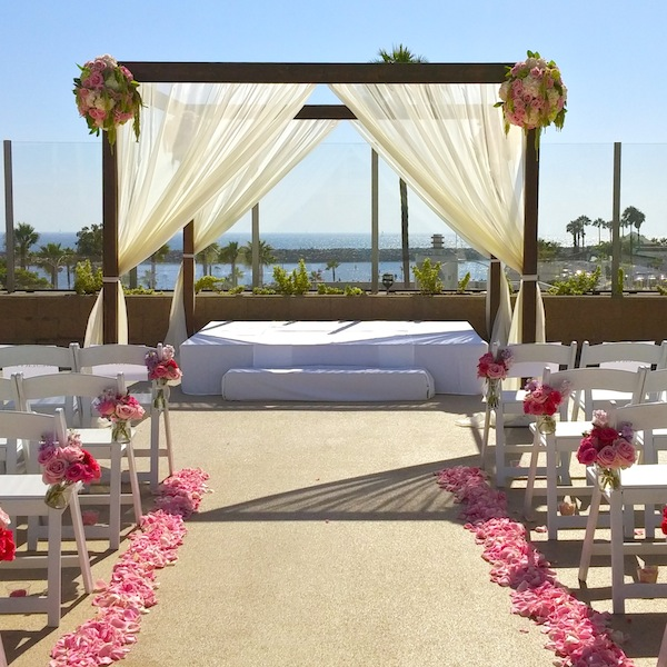 Pink accented wedding pergola overlooking yacht harbor in Los Angeles.