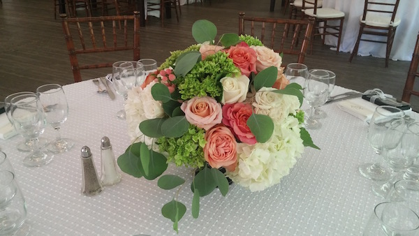 Rounded white and green centerpiece with coral roses.