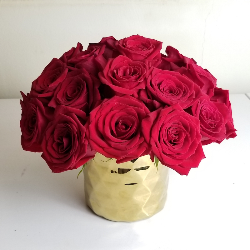 Red roses for holiday centerpieces in gold geometric vase
