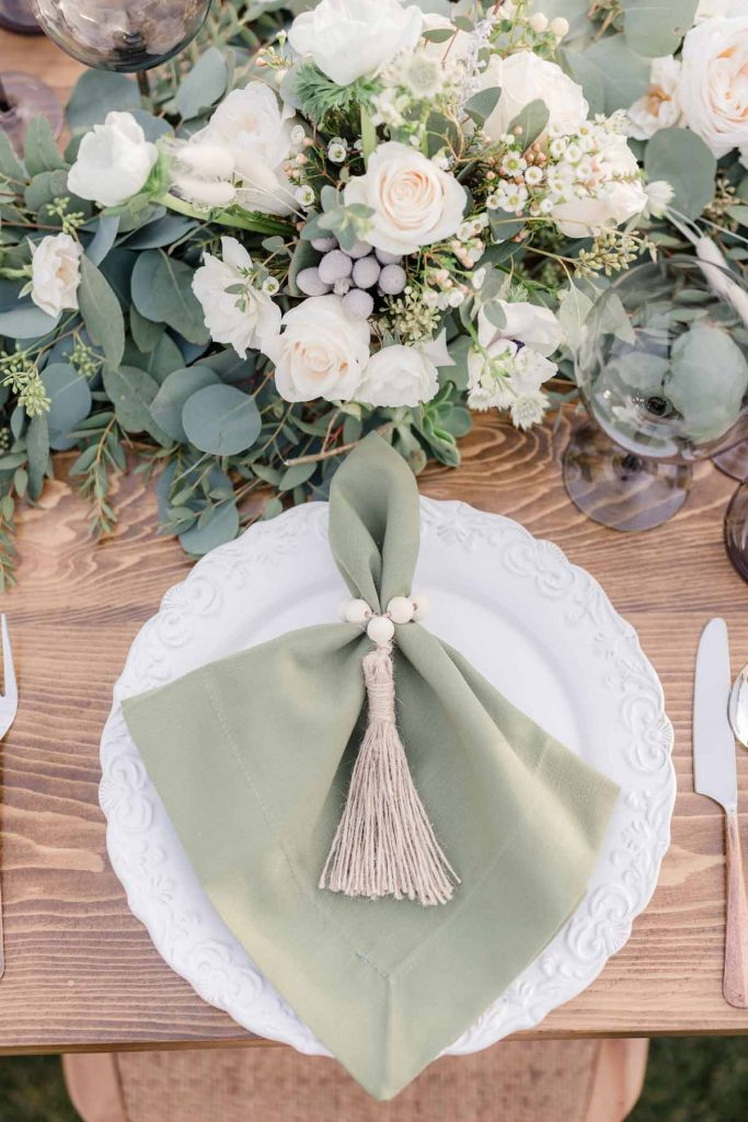 White Floral Centerpiece with Sage Green Napkin