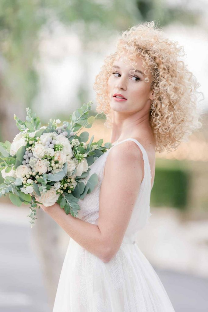 Bride with compact white and green bridal bouquet
